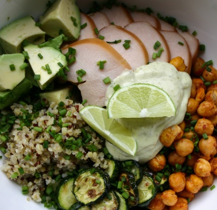 Quinoa bowl with smoked chicken, roasted zucchini, harissa roasted chickpeas and avocado, served with lime and a pesto- mayonnaise dressing