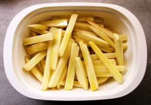 Hand cut potato chips, coated in olive oil and ready to be cooked