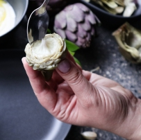 Using a spoon, remove the hairy choke from the base of the artichoke.